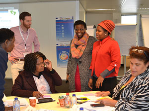 Background from left, CCL faculty Hughes Van Stichel and Sandrine Tunezerwe provide intense leadership training for women government leaders from five African countries.